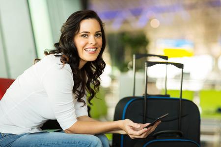 空港で彼女の飛行を待っている間タブレット コンピューターを使用して女性の旅行者の笑みを浮かべてください。