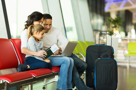 parents and little daughter using laptop at airport photo