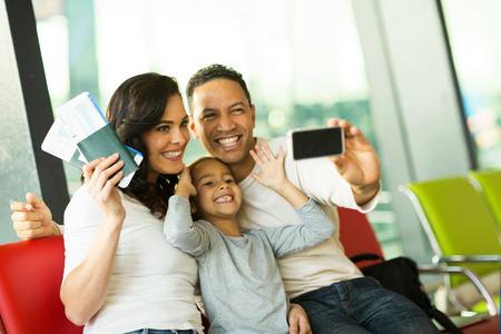 familia viaje: familia feliz en el aeropuerto toma autorretrato con el teléfono inteligente en el aeropuerto Foto de archivo
