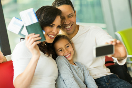wait: beautiful family taking selfie with smart phone while waiting for their flight at airport Stock Photo