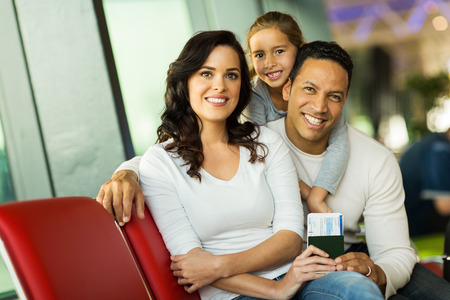lovely young family looking at the camera while waiting for flight at airport Stock Photo