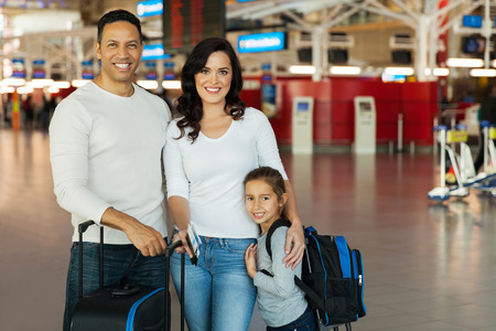 portrait of happy young family standing at airport photo