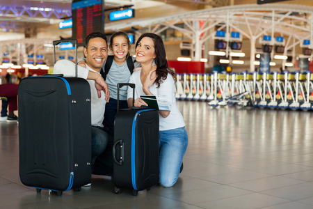 cheerful family with luggage bags at airport