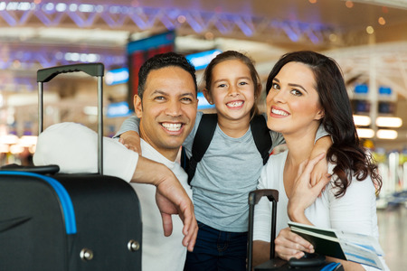 portrait of cute couple with their daughter at airport photo