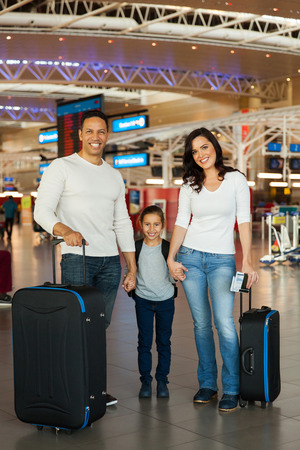 smiling family holding hands at airport photo
