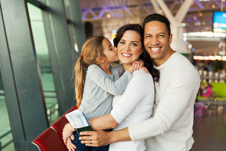 happy young couple: little girl kissing her mother at airport Stock Photo