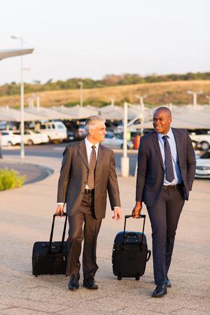 smart businessmen walking in airport parking lot photo