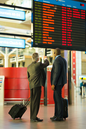 rear view of business partners checking flight information at airport photo