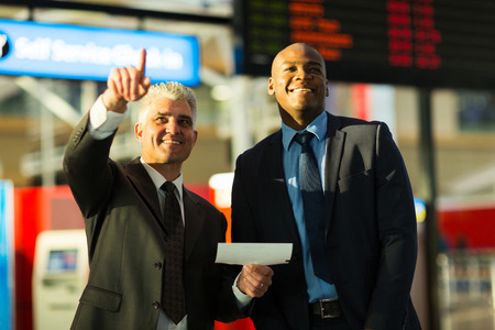 handsome business travellers pointing at flight information board photo