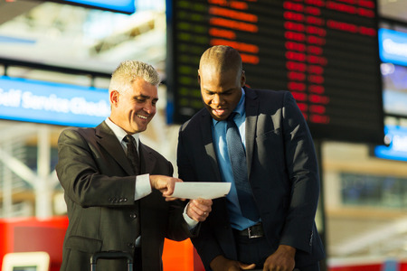 happy business travellers looking at air ticket in airport photo
