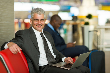 business traveler: portrait of happy mature business traveler using laptop at airport Stock Photo