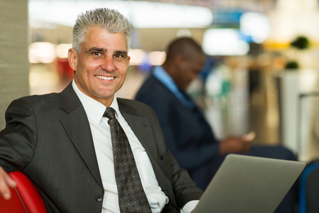 business lounge: handsome middle aged man waiting at airport lounge
