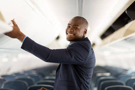 american airlines: cheerful african american businessman opening overhead locker on airplane Stock Photo