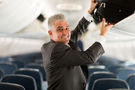 business traveler: portrait of middle aged business traveler putting luggage into overhead locker on airplane