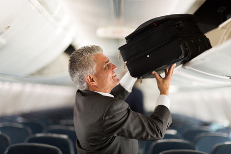 mature businessman putting luggage into overhead locker on airplane Stock Photo