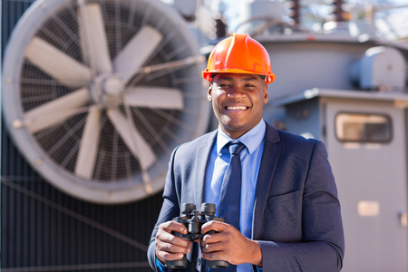 handsome african electrical manager with binoculars visiting substation photo