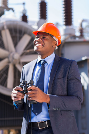 happy african american electrical businessman with binoculars at plant photo
