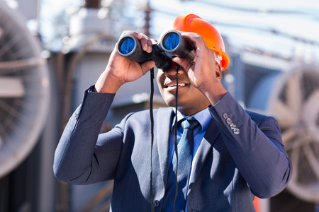 african electrician engineer using binoculars looking at electricity substation photo