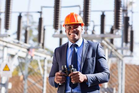 electricidad industrial: gerente industrial africano con binoculares en la planta de energía eléctrica Foto de archivo