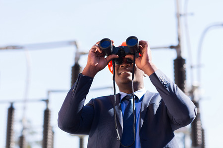 african american electrical manager using binoculars looking at substation photo