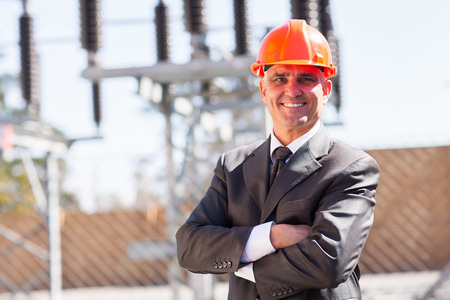 outdoor electricity: senior male industrial engineer in electricity substation with arms crossed