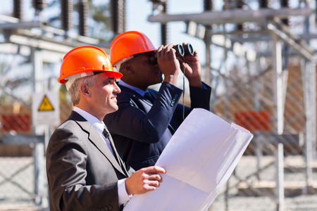 manager: two electrical managers with binoculars visiting power plant Stock Photo