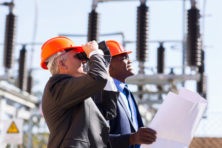 outdoor electricity: middle aged engineer and colleague with binoculars on electrical substation Stock Photo