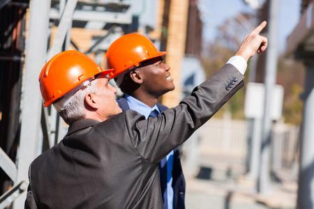 electricidad industrial: dos gerentes industriales varones que trabajan en la planta de energía eléctrica