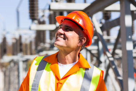 smiling mature male electrician in electrical substation