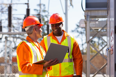 industrial plant: happy electricians using laptop computer in electrical substation