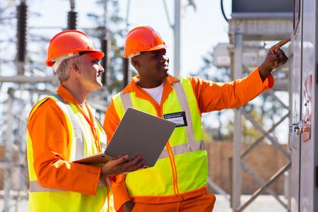 twee mannelijke ingenieurs werken in elektrische onderstation