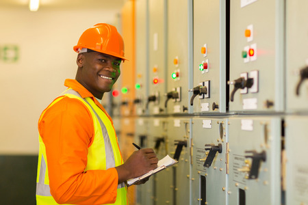 workplace safety: happy young african industrial technician taking machine readings