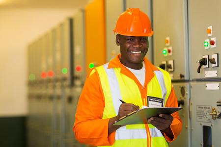 meter box: feliz afroamericano ingeniero de pie delante de panel de control Foto de archivo