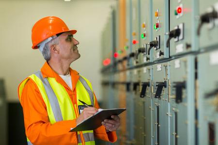 contador electrico: apuesto técnico mediados edad anotando los datos de ajuste de la máquina Foto de archivo