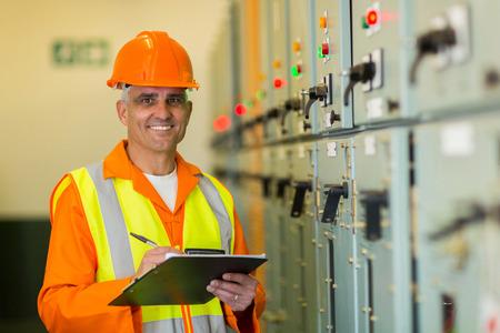 meter box: retrato de la sonrisa electricista maduro que trabaja en la sala de control