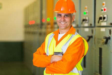 electricista: retrato de apuesto ingeniero el�ctrico de mediana edad con los brazos cruzados en la sala de control Foto de archivo