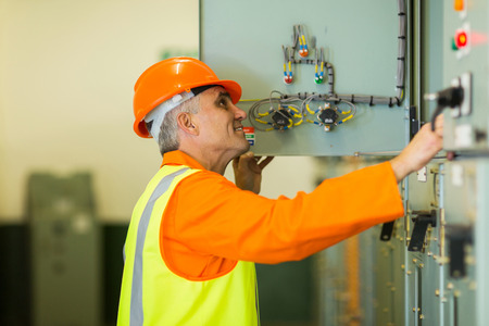 meter box: professional senior technician checking industrial machine control box Stock Photo