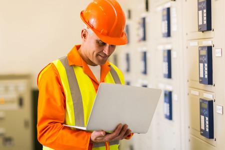 meter box: professional senior control room engineer using laptop Stock Photo