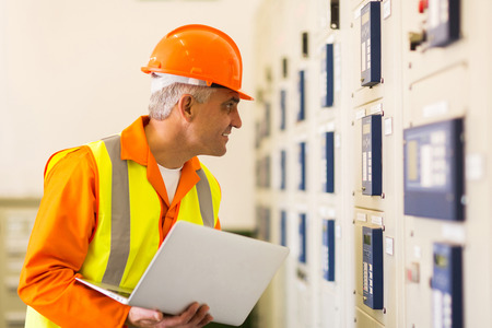 meter box: electricista industrial de mediana edad que trabaja en la sala de control de la planta de energ�a Foto de archivo