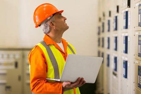 meter box: ingeniero el�ctrico de mediana edad con el ordenador port�til en la sala de control