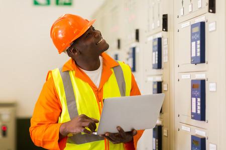 meter box: sonriente africano masculino ingeniero industrial usando la computadora port�til en la sala de control