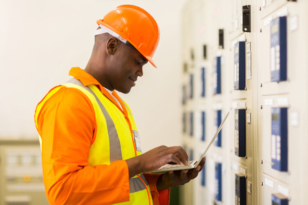 meter box: handsome young african control room engineer using laptop Stock Photo