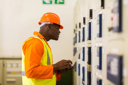meter box: professional african power company technical worker in control room Stock Photo