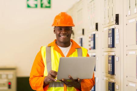 ingenieria el�ctrica: feliz ingeniero el�ctrico africano con el ordenador port�til en la sala de control de la planta de energ�a