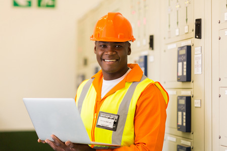 meter box: portrait of african engineer holding laptop in power plant control room