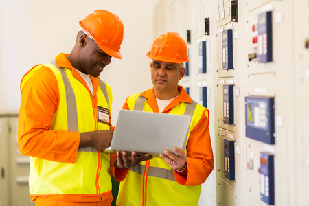 meter box: successful technicians using laptop in control room Stock Photo