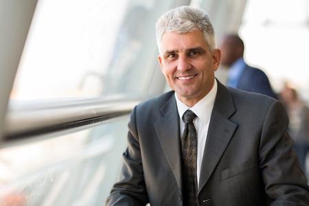 hombres maduros: apuesto hombre de negocios de mediana edad en la oficina moderna
