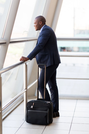 formal young african businessman with luggage at airport photo