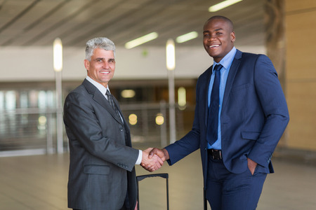african american handshake: portrait of business travellers greeting at airport Stock Photo