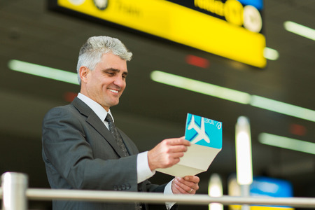 business traveller: smiling senior businessman looking at his air ticket at airport